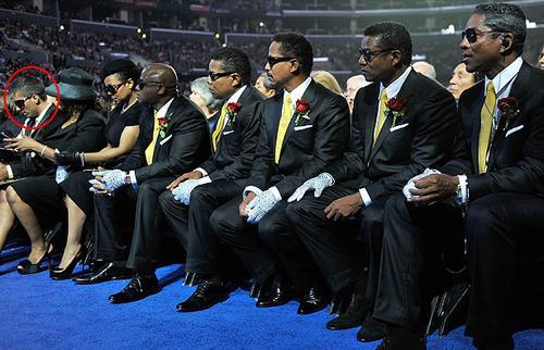 На церемонии прощания внебрачный сын Майкла - Омер Бхэтти сидит рядом с родственниками: (слева направо) сестры Джексона - Ребби и Джэнет, братья Ренди, Тито и Мэрлон, Джэки и Джереми