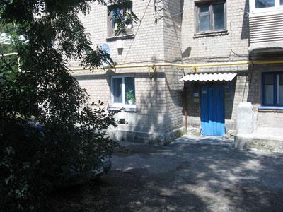 Двухэтажный дом и подъезд, где выросла Оля Корчанская. Квартира ее родителей на первом этаже с геранью на подоконнике