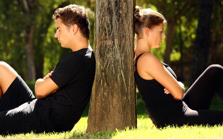 Мужчина и женщина, сидят спиной друг к другу