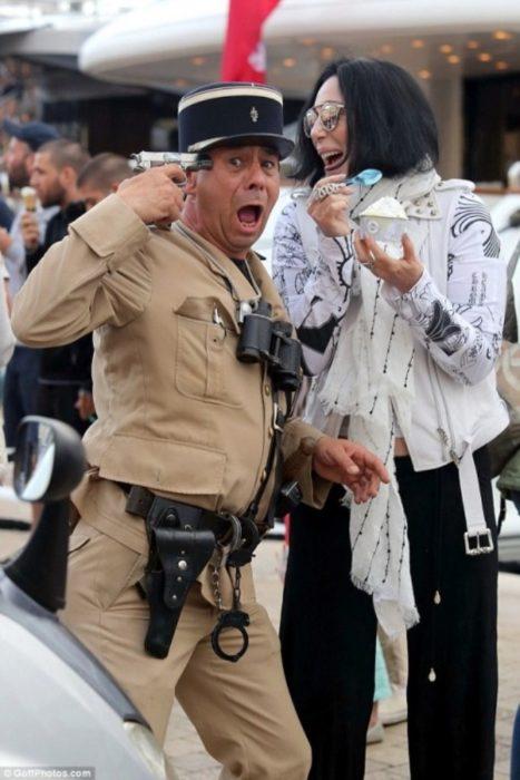 полицейский с пистолетом у виска и певица Шер