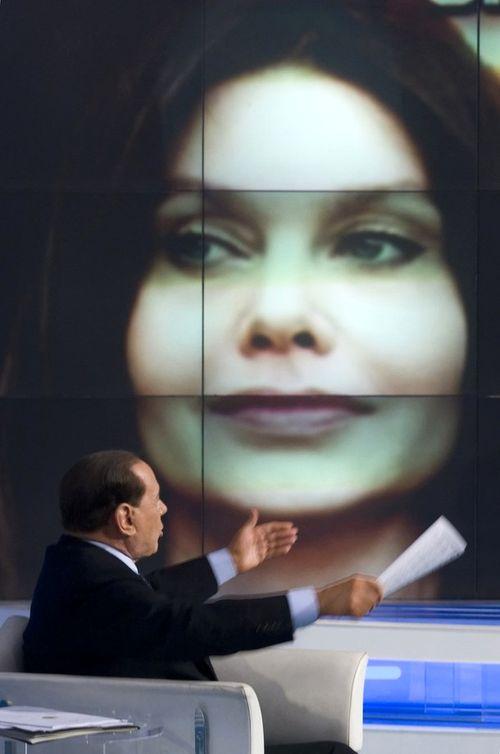 Cильвио Берлускони оправдывается на фоне портрета своей жены